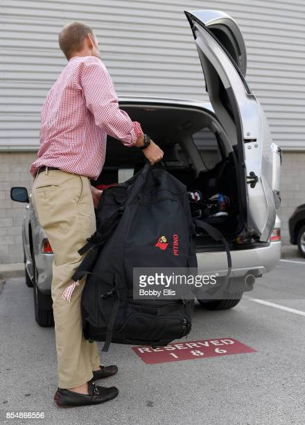 Jordan Sucher an assistant to Rick Pitino loads a bag with Pitino's name on it into his car outside of the Yum Practice Facility on September 27 2017...
