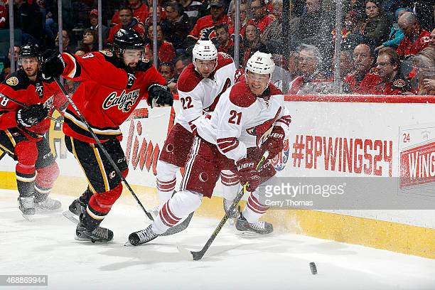 Jordan Szwarz of the Arizona Coyotes skates against David Schlemko of the Calgary Flames at Scotiabank Saddledome on April 7 2015 in Calgary Alberta...