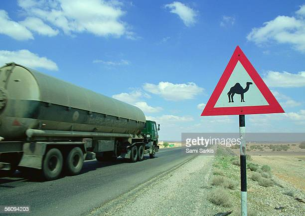 Jordan, tanker on road next to camel crossing sign