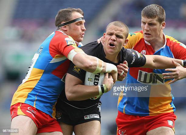 Jordan Tansey of Hull FC gets tackled by Tony Clubb and Rob Purdham of Harlequins during the Engage Rugby Super League Magic Weekend match between...