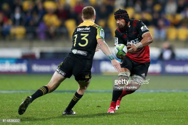 Jordan Taufua of the Crusaders passes under pressure from Jordie Barrett of the Hurricanes during the round 17 Super Rugby match between the...