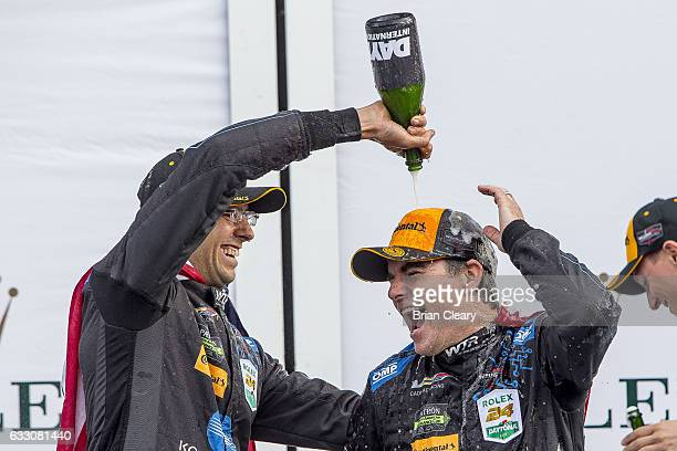 Jordan Taylor, L, douses Jeff Gordon with champagne in victory lane after winning the 24 Hours of Daytona at Daytona International Speedway on...