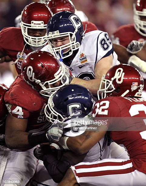 Jordan Todman of the Connecticut Huskies is tackled by Jeremy Beal and Jamell Fleming of the Oklahoma Sooners in the first half during the Tostitos...