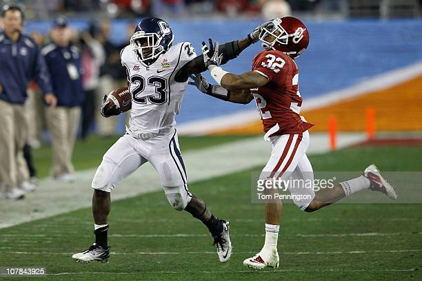 Jordan Todman of the Connecticut Huskies stiff arms Jamell Fleming of the Oklahoma Sooners in the second quarter during the Tostitos Fiesta Bowl at...