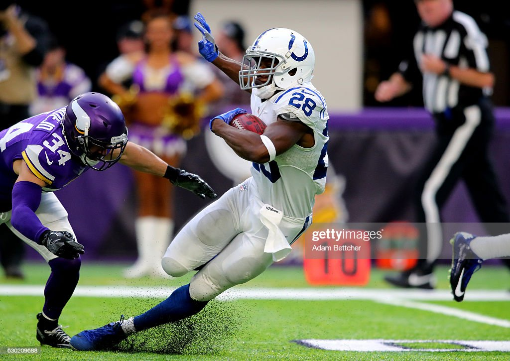 Jordan Todman #28 of the Indianapolis Colts carries the ball while Andrew Sendejo #34 of the Minnesota Vikings dives to tackle him in the third quarter of the game on December 18, 2016 at US Bank Stadium in Minneapolis, Minnesota.