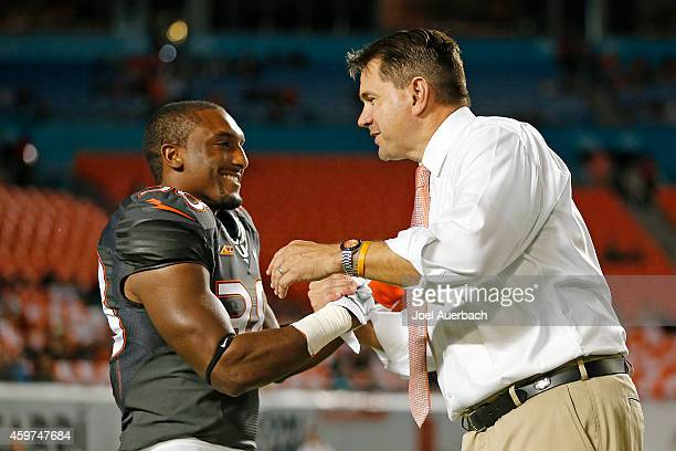 Jordan Tolson is greeted by Head coach Al Golden of the Miami Hurricanes as part of the senior night ceremonies prior to the game against the...