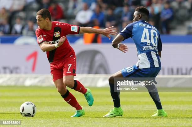 Jordan Torunarigha of Berlin battles for the ball with Chicharito of Leverkusen during the Bundesliga match between Hertha BSC and Bayer 04...