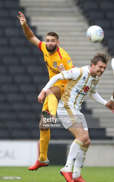 Jordan Turnbull of Northampton Town heads the ball away from Alex Gilbey of Milton Keynes Dons during the Sky Bet League Two match between Milton...