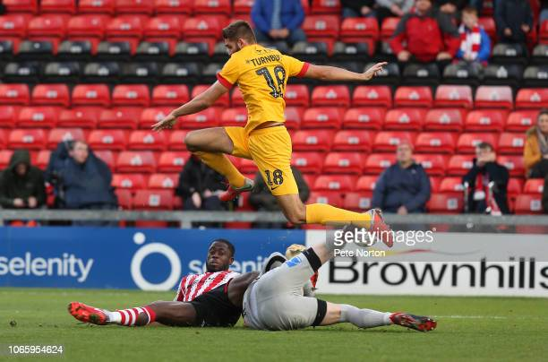 Jordan Turnbull of Northampton Town jumps over David Cornell as he saves at the feet of John Akinde of Lincoln City during the FA Cup First Round...