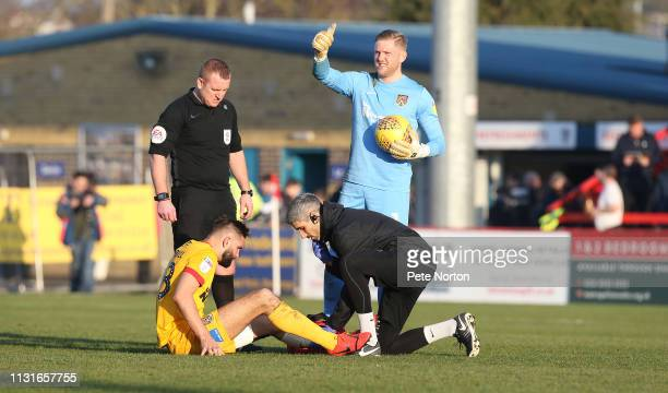 Jordan Turnbull of Northampton Town receiving treatment from physio Nacho Herrando as referee Lee Swabey and team mate David Cornell look on during...