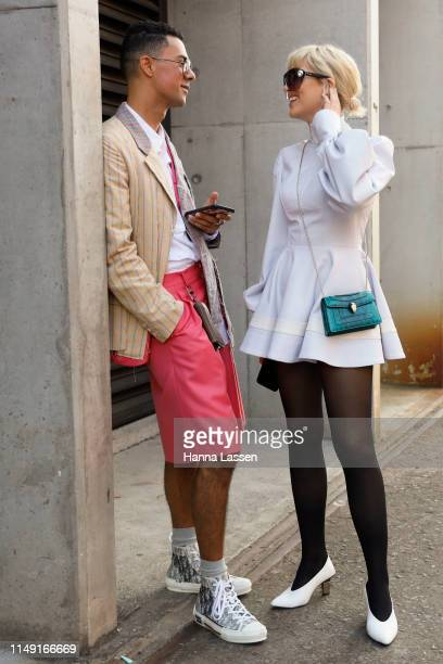 Jordan Turner wearing COMME des GARÇONS suit, Dior bag and Dior sneakers and Violet Atkinson wearing Leo & Lin dress, Bvlgari bag and Miu Miu...