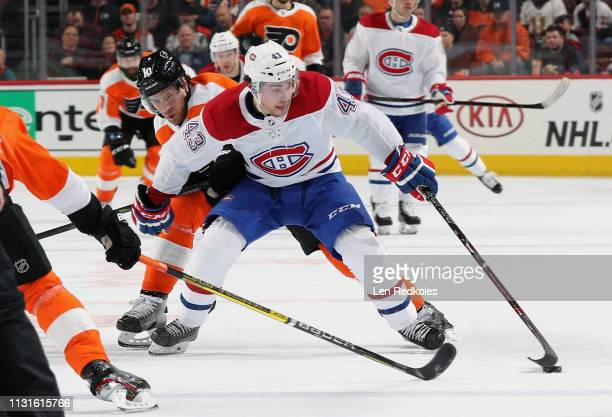 Jordan Weal of the Montreal Canadiens attempts to control the puck while being pursued by Corban Knight of the Philadelphia Flyers on March 19 2019...
