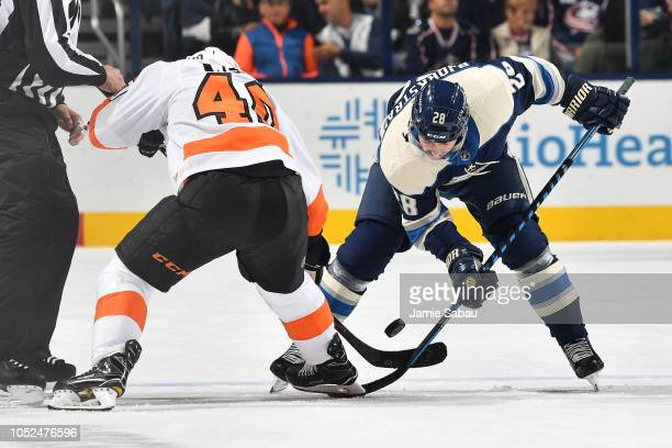 Jordan Weal of the Philadelphia Flyers and Oliver Bjorkstrand of the Columbus Blue Jackets battle for control of a faceoff during the first period on...