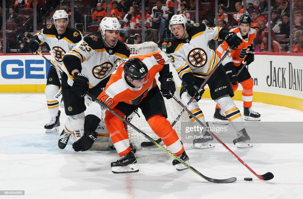 Jordan Weal #40 of the Philadelphia Flyers attempts to control the loose puck against Zdeno Chara #33 and Charlie McAvoy #73 of the Boston Bruins on December 2, 2017 at the Wells Fargo Center in Philadelphia, Pennsylvania. The Bruins went on to defeat the Flyers 3-0.