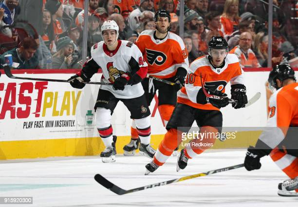 Jordan Weal of the Philadelphia Flyers keeps his eye on the airborne puck against JeanGabriel Pageau of the Ottawa Senators battle for the puck on...