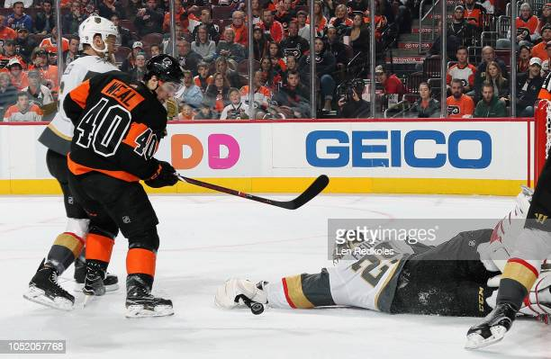 Jordan Weal of the Philadelphia Flyers keeps his eyes on the loose puck as goaltender MarcAndre Fleury of the Vegas Golden Knights lunges out of his...