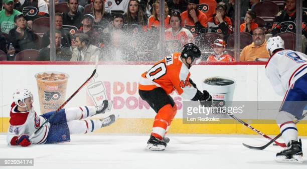 Jordan Weal of the Philadelphia Flyers skates the puck against Jordie Benn and Charles Hudon of the Montreal Canadiens on February 20 2018 at the...