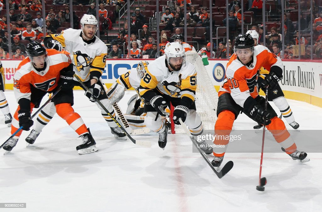 Jordan Weal #40 of the Philadelphia Flyers skates with the puck in the corner against Kris Letang #58 of the Pittsburgh Penguins on January 2, 2018 at the Wells Fargo Center in Philadelphia, Pennsylvania. The Penguins went on to defeat the Flyers 5-1.