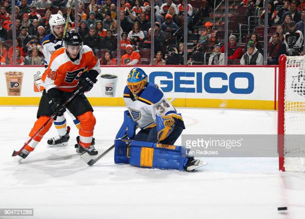 Jordan Weal of the Philadelphia Flyers waits atop the crease for a pass against Jake Allen and Joel Edmundson of the St Louis Blues on January 6 2018...