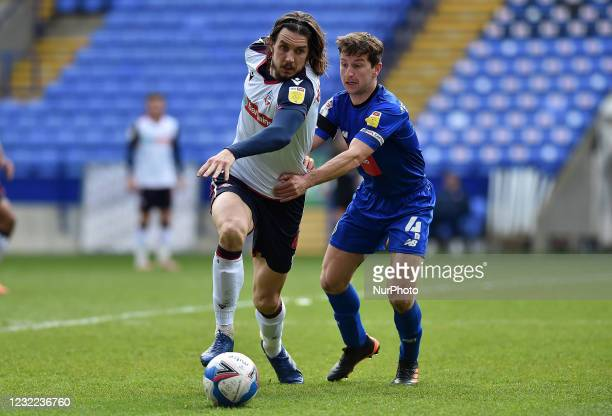 Jordan Williams of Bolton Wanderers tussles with Josh Falkingham of Harrogate Town during the Sky Bet League 2 match between Bolton Wanderers and...