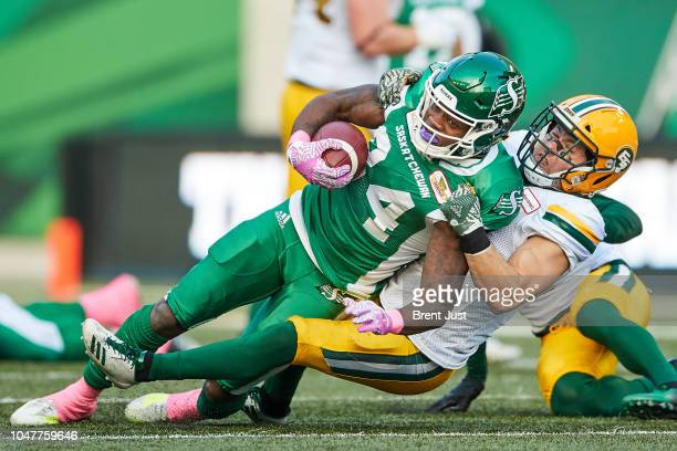 Jordan WilliamsLambert of the Saskatchewan Roughriders is tackled after a catch by JC Sherritt of the Edmonton Eskimos in the game between the...