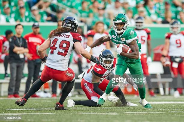 Jordan WilliamsLambert of the Saskatchewan Roughriders looks to avoid Alex Singleton of the Calgary Stampeders after making a catch in the game...