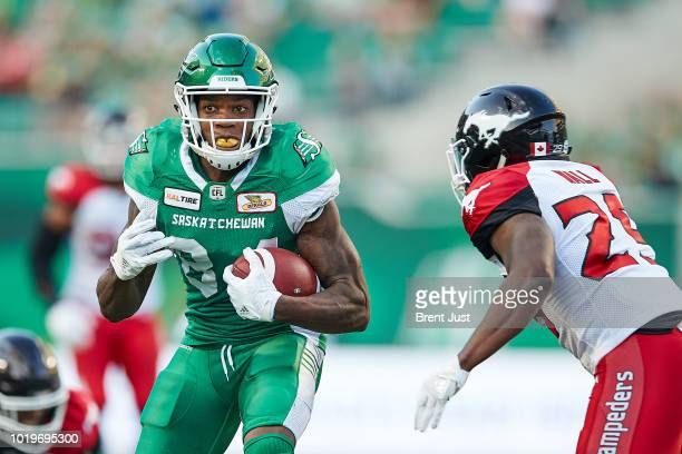 Jordan WilliamsLambert of the Saskatchewan Roughriders runs after a catch and tries to avoid Jamar Wall of the Calgary Stampeders in the game between...