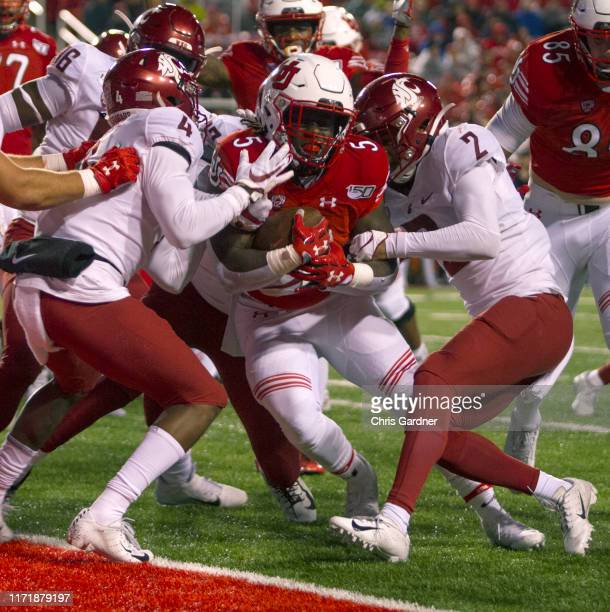 Jordan Wilmore of the Utah Utes is held on the goal line by Marcus Strong Derrick Langford and Bryce Beekman of the Washington State Cougars at...
