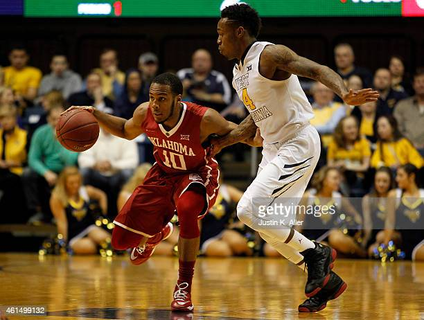 Jordan Woodard of the Oklahoma Sooners drives the ball down court against Daxter Miles Jr #4 of the West Virginia Mountaineers during the game at the...