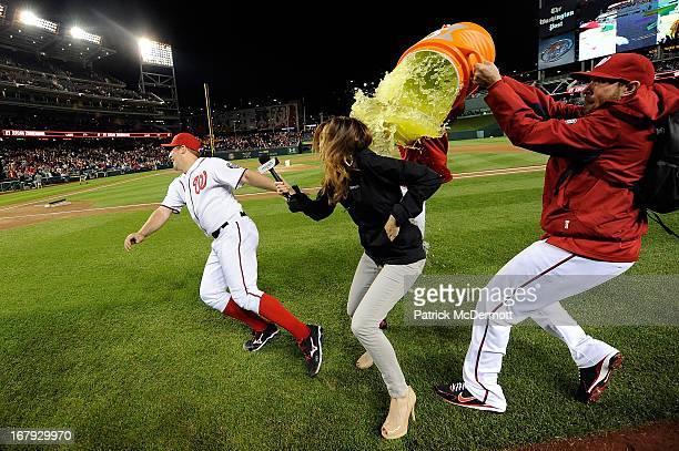 Jordan Zimmermann of the Washington Nationals and MASN's sideline reporter Julie Alexandria are dunked with gatorade by Drew Storen and Ryan Mattheus...
