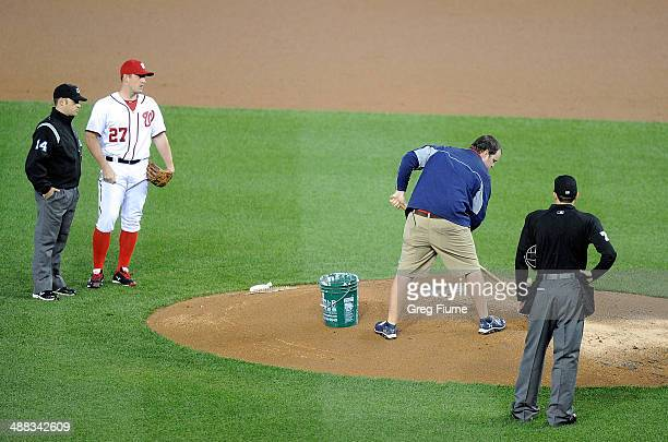Jordan Zimmermann of the Washington Nationals watches the grounds crew try to dry the pitcher's mound during the third inning against the Los Angeles...