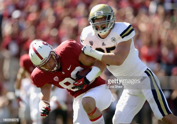 Jordan Zumwalt of the UCLA Bruins hits Devon Cajuste of the Stanford Cardinal at Stanford Stadium on October 19 2013 in Palo Alto California