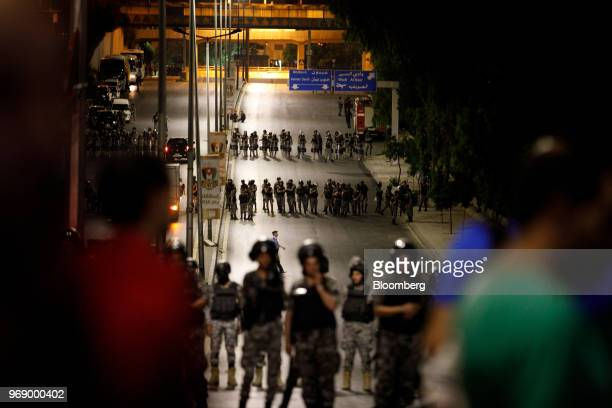 Jordanian anti riot police stand in lines to protect the prime minister's office during a demonstration against a draft income tax law in Amman...