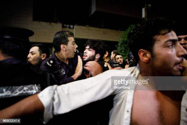 Jordanian antiriot police push back protesters during a demonstration against a draft income tax law near the prime minister's office in Amman Jordan...