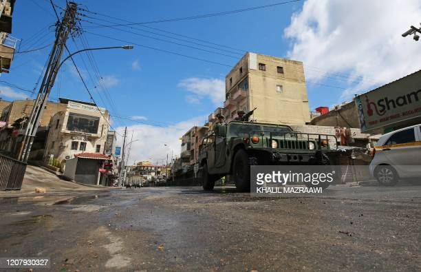 Jordanian army vehicles drive through a street in capital Amman during a nationawide curfew imposed by the authorities in order to control the spread...