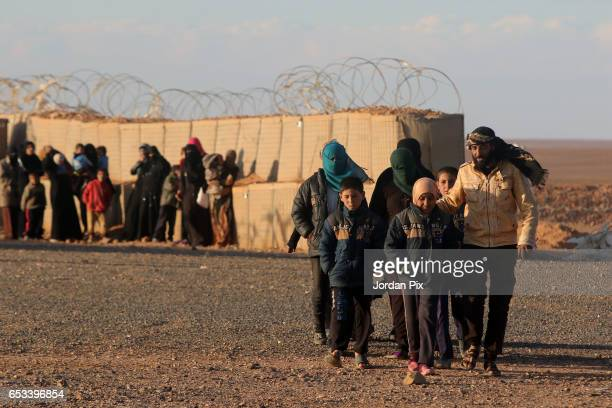 Jordanian border soldiers allow refugees at the Al Roqban camp in the noman's zone between Syria and Jordan to get medical attention during a media...