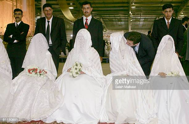 Jordanian brides and grooms take their place during a mass wedding for needy people July 30 2004 in Amman Jordan About 150 Muslim couples were...