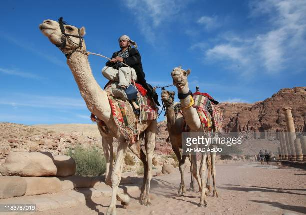 A Jordanian cameleer rides while dragging along camels to rent for tourists in the archaeological city of Petra south of the capital Amman on...