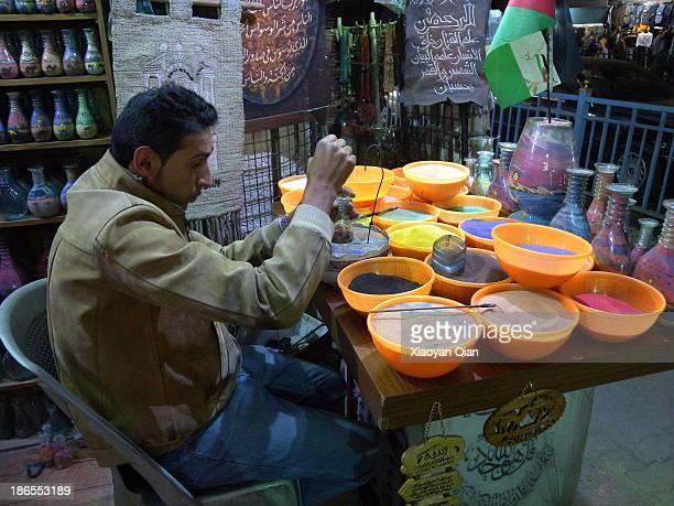 Jordanian craftsman doing sand paintings in bottles in Amman Jordan