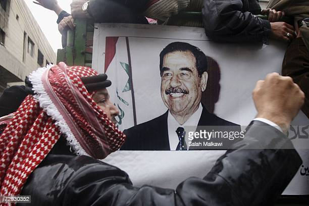 Jordanian demonstrators hold pictures of former Iraqi President Saddam Hussein during a protest against his execution on January 05 2007 in Amman...