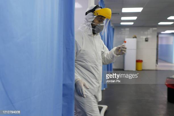 Jordanian doctor tests the sample of a patient in one of the country's official coronavirus testing sites on March 15 2020 in Amman Jordan After...