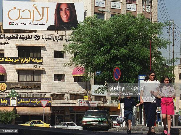 Jordanian family walks through the streets of Amman 21 June 2000 under a banner promoting Jordan as a 'small country with big ideas' to attract...