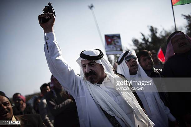 A Jordanian government supporter shoots in the air with a pistol during a gathering in support of King Abdullah II in the capital Amman March 26 2011...