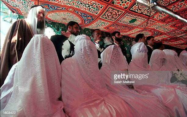 Jordanian grooms and brides prepare for a mass wedding ceremony at a school July 20 2001 in Amman The wedding ceremony for 72 couples was organized...