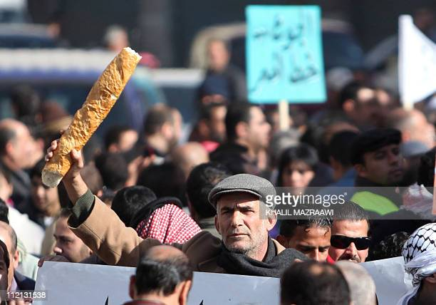 A Jordanian man brandishes a loaf of bread during a protest in Amman on january 14 2011 Thousands of Jordanians took to the streets of Amman and...