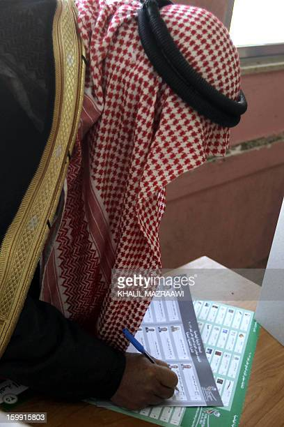 A Jordanian man marks his ballot at a polling station in the Palestinian refugee camp of Baqaa north of Amman on January 23 2013 Jordanians are...