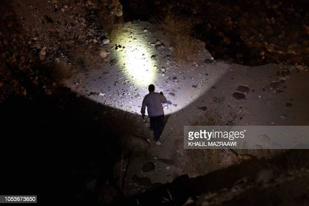 A Jordanian man searches the site of a bus accident near the Dead Sea in Jordan on October 25 2018 Flash floods in Jordan swept away a school bus on...