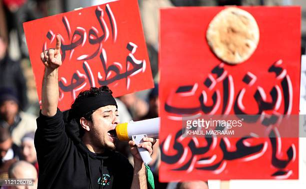A Jordanian man shouts slogans next to a loaf of bread hanging on a placard reading 'where are you my dear' during a protest in Amman on january 14...