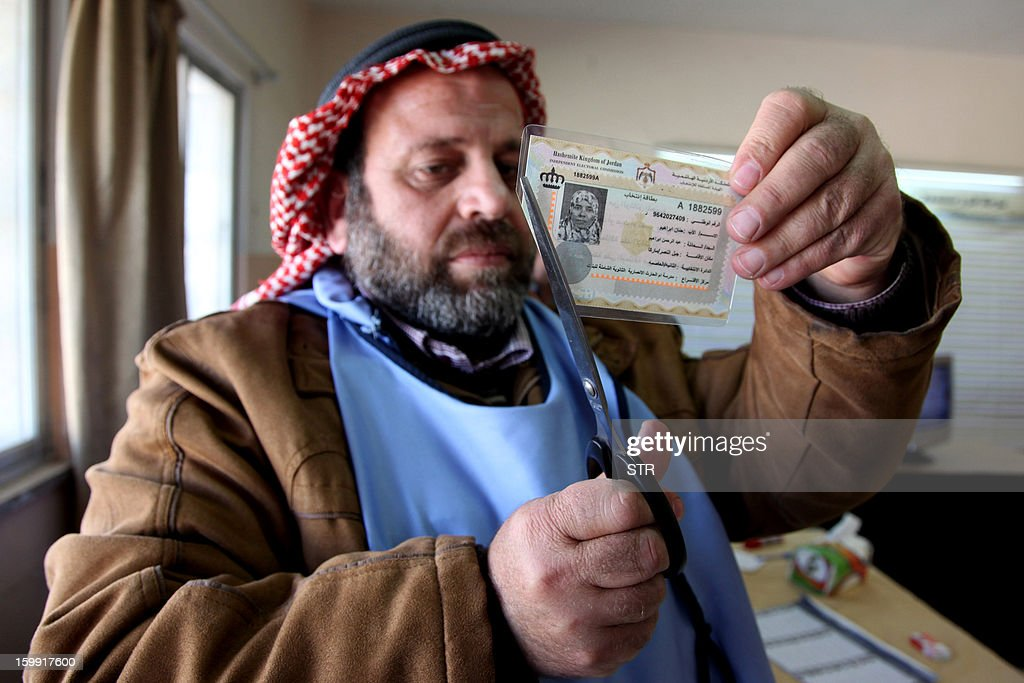 A Jordanian observer cuts the voter ID card of a woman after she cast her ballot at a polling station in Amman on January 23, 2013. Jordanians are voting in a parliamentary poll snubbed by Islamists who have staged strident pro-reform protests and who have already slammed what is expected to be an opposition-free body as illegitimate.