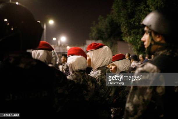 Jordanian police women stand guard beside anti riot police during a demonstration against a draft income tax law near the prime minister's office in...